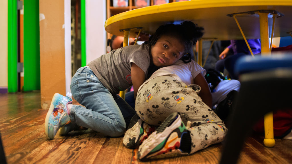 Justice Buress, 4, hides under a table while demonstrating a drill at Little Explorers Learning Center in St. Louis. Tess Trice, head of the day care program, carries out monthly drills to train the children to get on the floor when they hear gunfire.