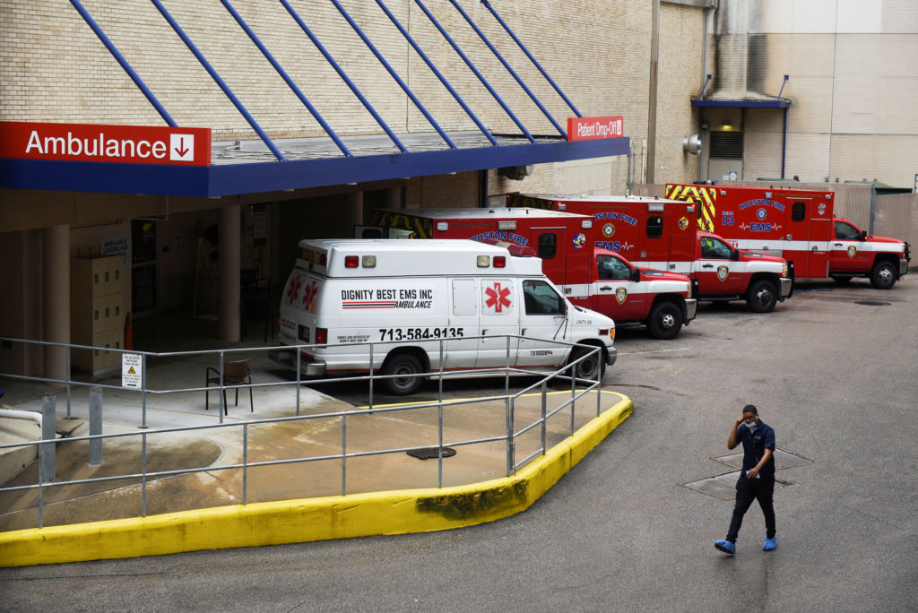 A medical worker walks past a row of ambulances parked outside of Houston Methodist Hospital in Houston, Texas, on June 22. The hospital is treating a current surge of COVID-19 cases.