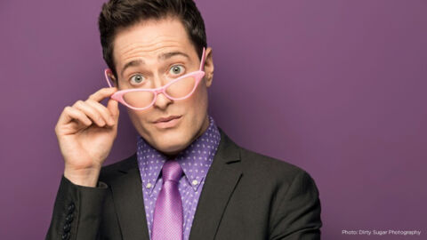 A man in suit with purple shirt and pink tie wears pink eyeglasses on the bridge of his nose, looking at camera quizzically.