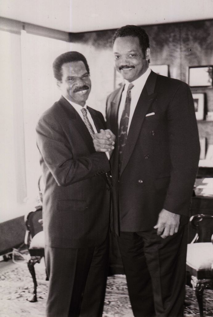 Reginald F. Lewis and Rev. Jesse Jackson shake hands.