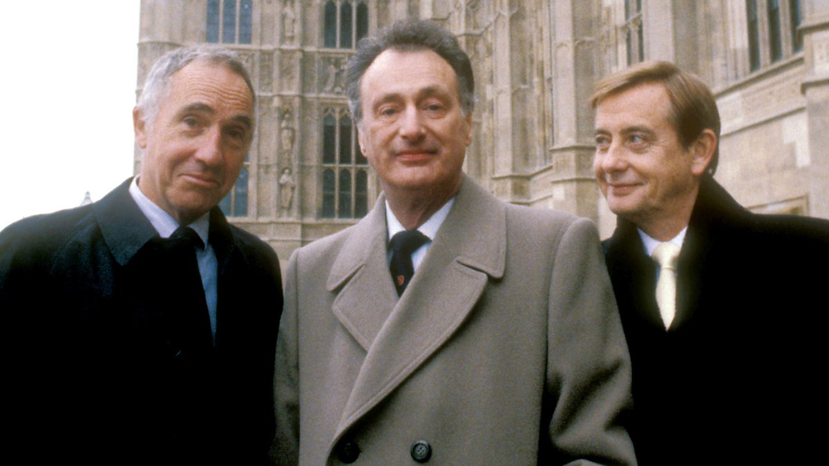 Three older white men in trenchcoat style jackets smile for camera