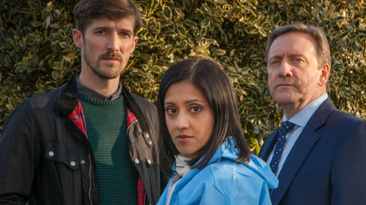 Three people pose for camera but look serious. A tall you man with a beard and moustasche in casual dress. A young South Asian woman in a sky blue windbreaker; an older man in a suit and tie. Behind them is a tall, green shrub or bush