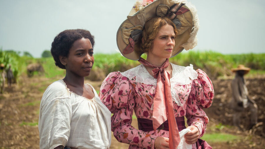 A black woman with white cotton drawstring shirt and brown skirt stands next to white woman in a fine pink dress and very large wide-brimmed hat in a plantation field.